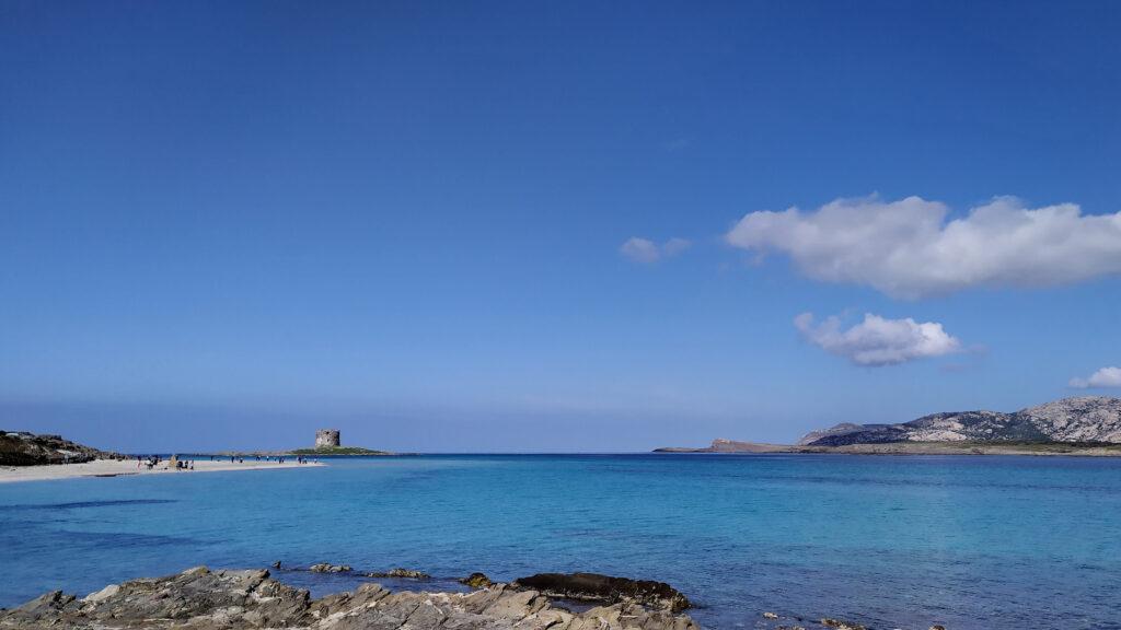 spiaggia pelosa e sullo sfondo la torre